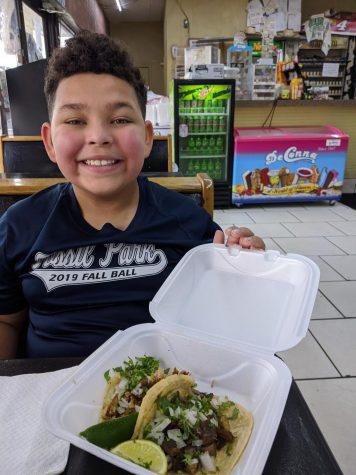 Student posing with tacos